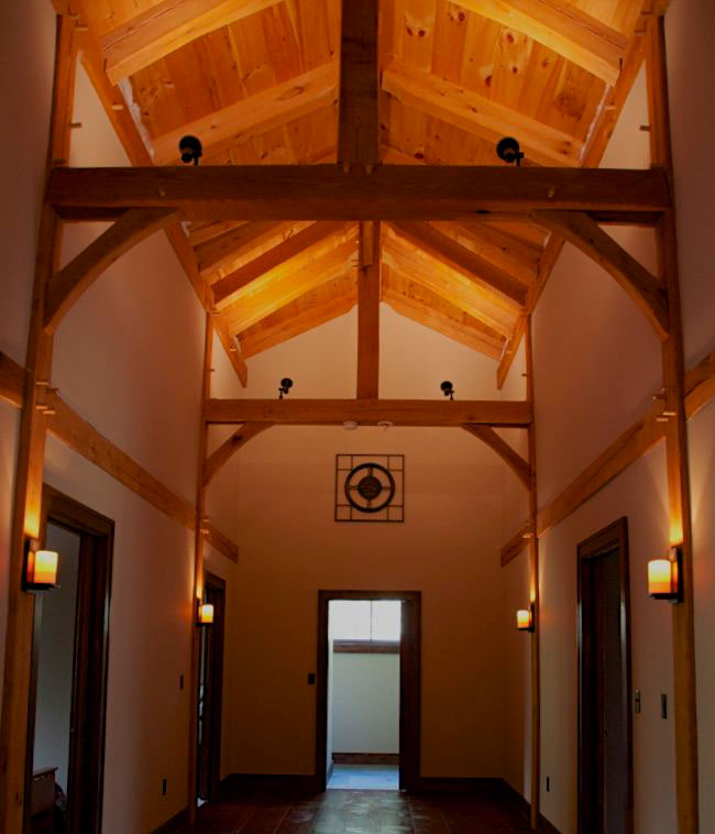 This timber frame hallway adds drama to the second floor of this residence.