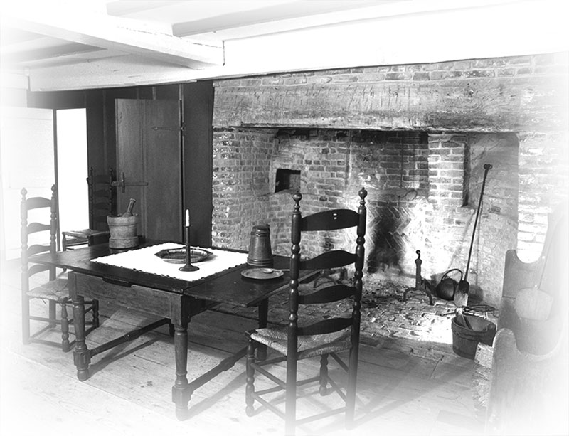 This interior photo of the oldest house in Nantucket shows a table with straight-back chairs drawn close to the massive fireplace.