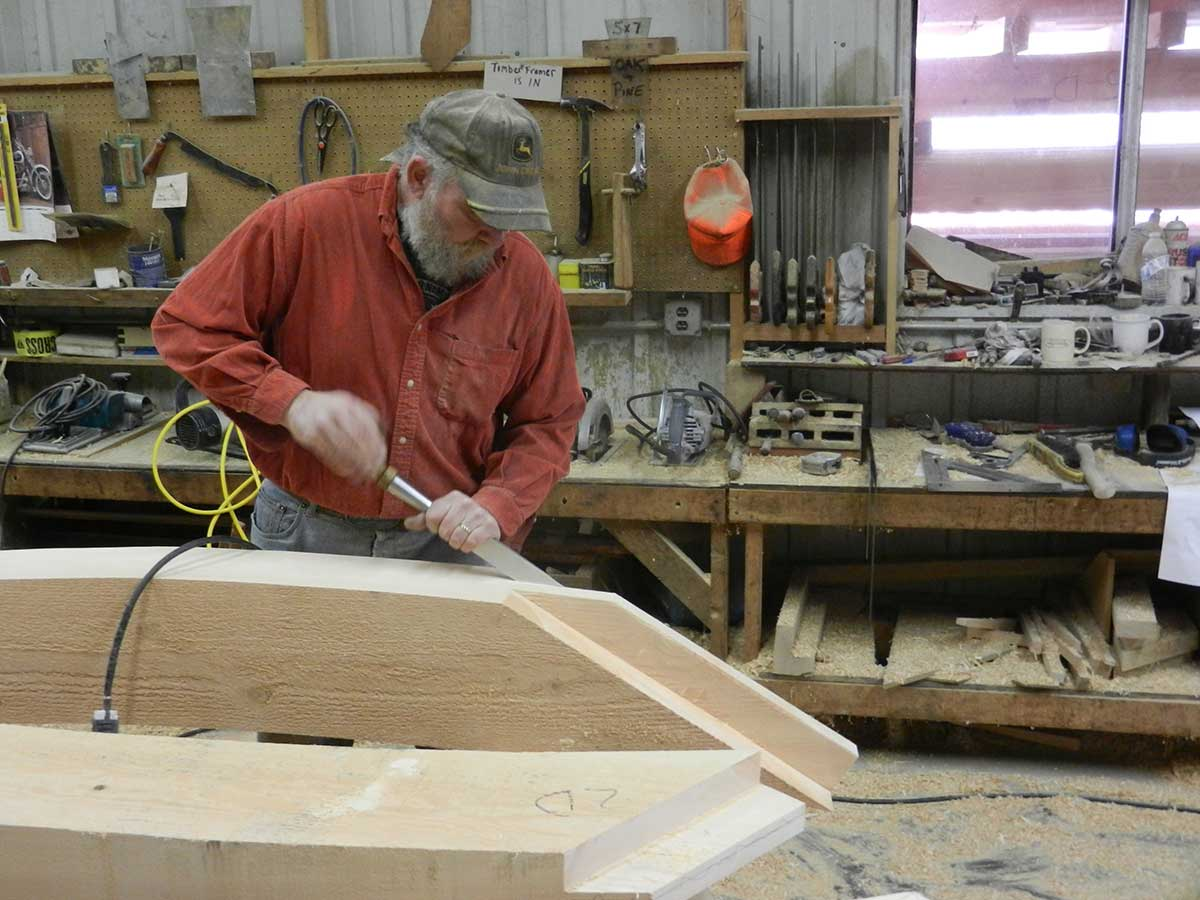 A craftsmen cuts the joint with a hand-held chisel